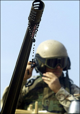 photo: a rosary hanging from an American machine gun barrel