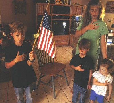 Photo: three home-schooled children and their mother hold their hands over their hearts and hold up a United States flag in their living room