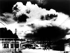 photo: a photo of the mushroom cloud rising over Nagasaki, taken from ground level in the city