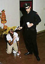 photo: white frat brothers, one in blackface, pose with the student in blackface kneeling on the floor and a student dressed as a cop pointing a prop gun at his head. Ole Miss, Halloween 2001.