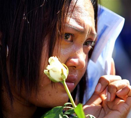 Pimchai Chudum holds a rose in memory of her brother during a tsunami commemoration ceremony in Khao Lak, Thailand