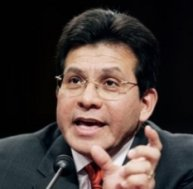 Alberto Gonzales leans his blocky-shaped head forward during testimony