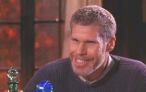Ron Perlman's character leans his blocky-shaped head forward and grins a predatory grin while leaning forward in The Last Supper