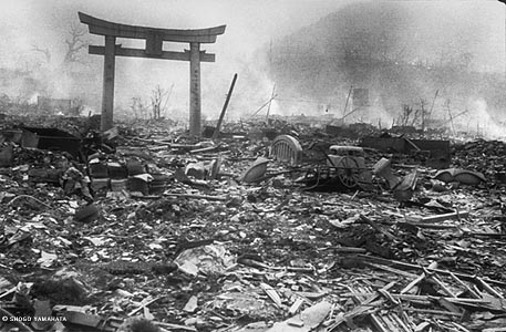 Here is a city street completely reduced to rubble, with fires smoldering in the background and smoke hanging in the air. A single Shinto gateway remains standing over the rubble.