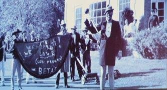Here is an old black and white photo of several white students in minstrel-show blackface, smiling at the camera and holding a banner reading 'We love the Betas.'