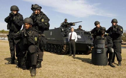 Here is a photograph of several men in dark uniforms with helmets and body armor, in combat posture, with assault rifles pointed directly at the camera. They are posed in front of a large tank. One man is standing in front of the tank, smiling, in a normal suit and tie.