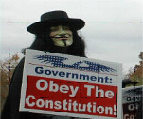 "Here is a picture of a person dressed up as V from V for Vendetta holding a sign that reads ""Government: Obey the Constitution"""