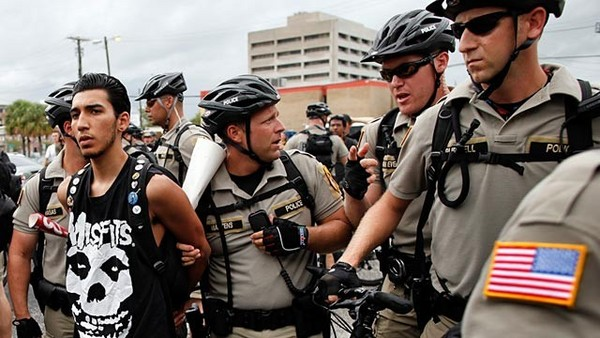 (A photograph of a huge crowd of bicycle cops arresting a young man in a Misfits t-shirt, while other bike cops hold onlookers off at a distance.)