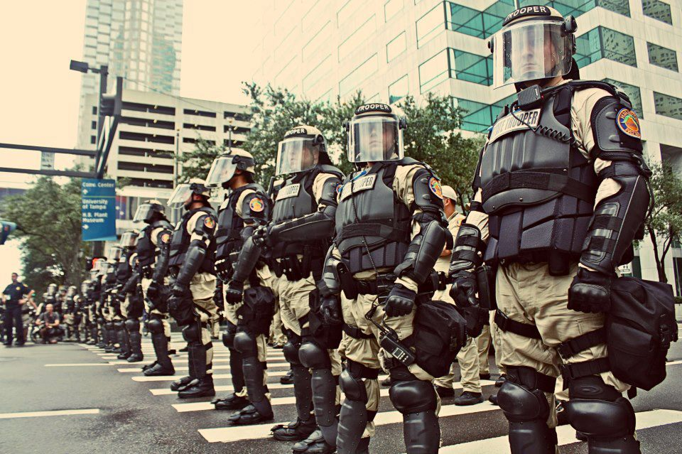 (A photograph of a line of State Troopers in heavy body armor and riot gear.)