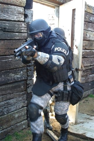 Here's a photo of a heavily armored soldier bursting through the door and pointing a shotgun at the camera. On his arm there's a band reading POLICE.