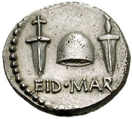 Here's a photo of a silver coin with the caption EID MAR. Above the caption are two daggers, flanking a Liberty Cap to the left and the right.