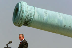 photo: George w. Bush, delivering a speech under a massive cannon
