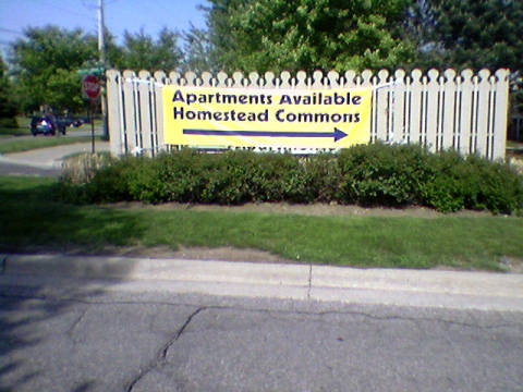 "I have a photo of a large yellow banner draped over a fence on an island in the middle of the street, reading: ""Apartments Available / Homestead Commons"""
