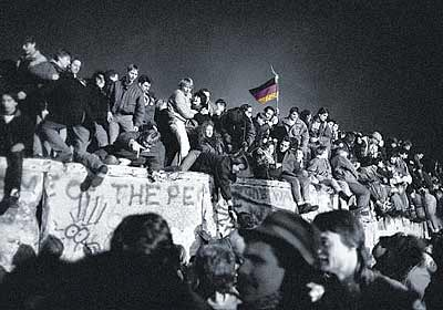 Here's a photo of Germans standing on top of the Berlin Wall as it is being torn down.