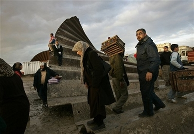 Here's a photo of Gazans stepping over a destroyed border wall.