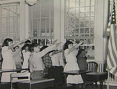 Here's a photograph of a group of white elementary school chidren, of about the same age, with their arms also raised--towards an American flag in the far right of the photograph.