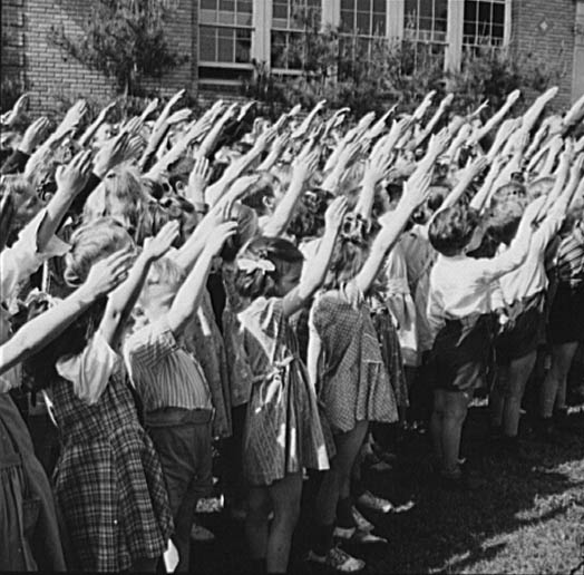A crowd of white elementary school children with their right arms extended diagonally upwards.