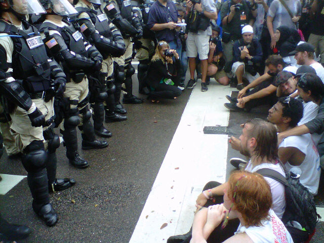 (A photograph of a line of police in body armor and riot gear standing in front of a group of seated, unarmed protesters in casual dress.)
