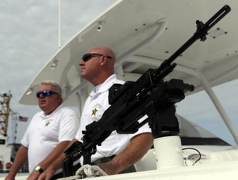 (A photograph of two police officers on a boat with a mounted carbine pointing off toward the top of the photo.)