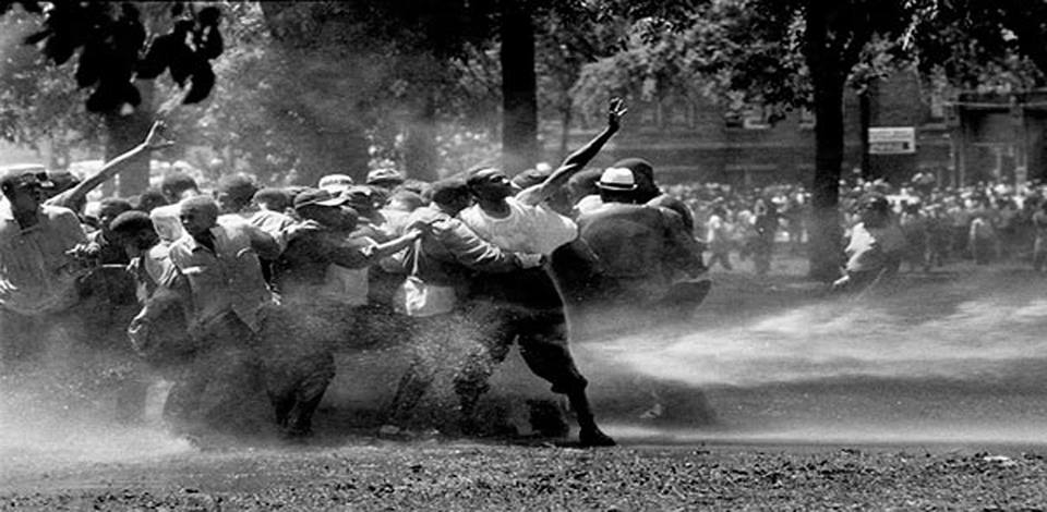 Here's a black and white  photo of a group of black youths, standing in a park with their arms outstretched, facing the blast of a water cannon from the right.